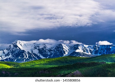 View of the snow-covered slopes of the North Chui mountain range from the kurai steppe and the Altai taiga. The Altai mountains, Kosh Agach district, southern Siberia, Russia