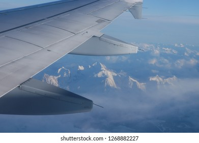 View of the snowy alps from the window of a commercial airplane