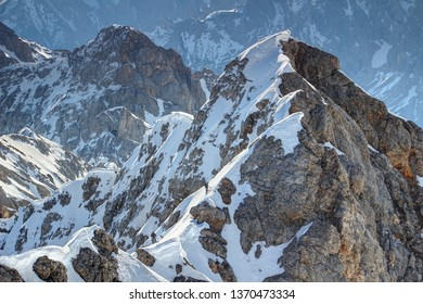 View of snowy climbing route Jubilaumsgrat from Zugspitze in Wetterstein range with two tiny mountaineers ascending narrow rocky ridges, Bavarian Alps Northern Limestone Alps Bayern Germany Europe