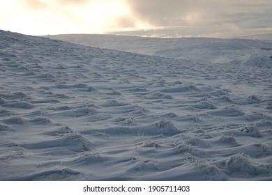 view of snowy mountainous landscape under orangish sky