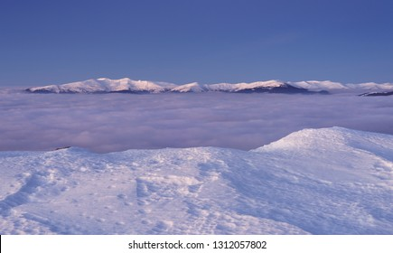 View to snowy mountains range above the clouds. Svydovets masif, Ukraine