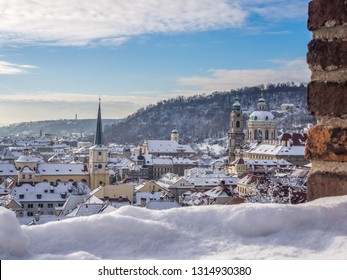 The view of snowy Old Town buildings captured from the Prague Castle outlook in the winter morning. Prague, Czech Republic.