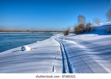 View of  snowy river.Along  coast are traces of skis.