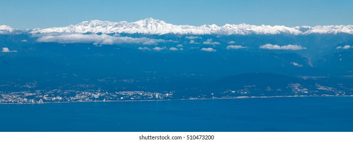 View of Sochi (Russia), the Black Sea and the snow-capped Caucasus Mountains on board an airplane.