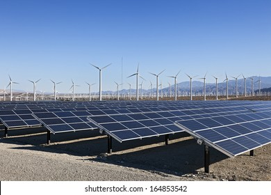 A View of Solar Panels and Wind Turbine in the Field