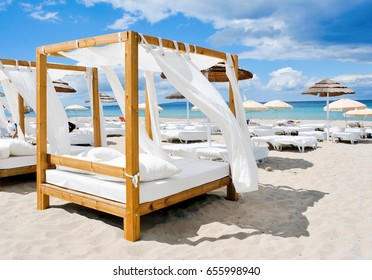 view of some beds in a beach club in a white sand beach in Ibiza, Spain