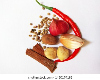 a view of some cooking spices consisting of red onion, garlic, pepper, cinnamon, candlenut and nutmeg.