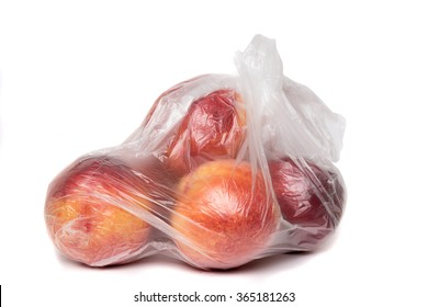 View of some peaches inside a plastic bag isolated on a white background.