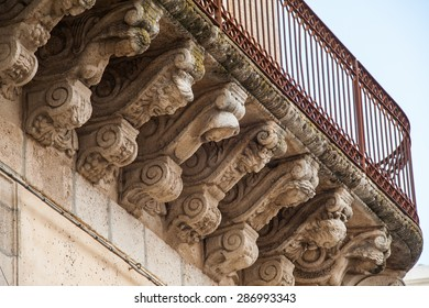 View of some stone mascarons under the balcony of a baroque palace in Caltagirone, Sicily