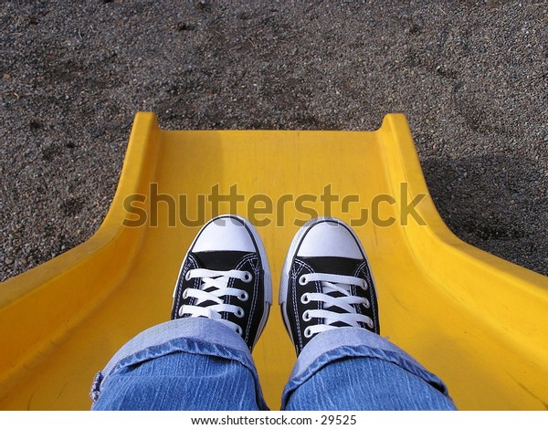 A view of someone's shoes as they are sitting on a slide.