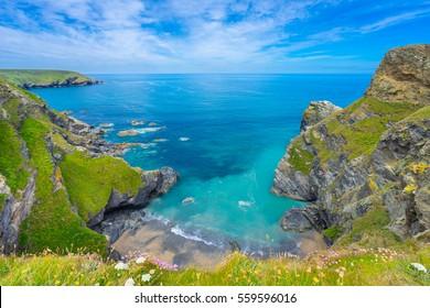 Blick auf die Südküste von Devon, England, im Sommer mit klarem Wasser, blauem Himmel und Gras.