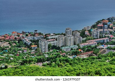 View of the Southern Coast of Crimea from the observation deck of the Orthodox Church in Foros. Houses and hotels along the coast and mountains with evergreen and deciduous trees and shrubs.