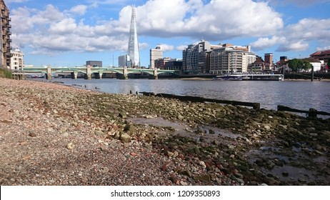 View of Southwark Bridge and the Shard from the Thames foreshore at Millenium Bridge, London
