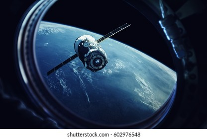 View from spaceship porthole. Earth and spacecraft. Elements of this image furnished by NASA