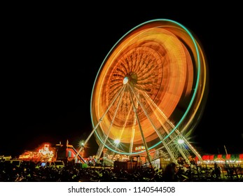 view of spinning ferris wheel (observation wheel) moving with light-trails in canival fun fair at night.