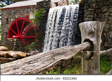 View of a split rail fence with a grist mill and waterfall in the background