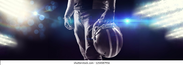 View of spotlights against american football player standing with helmet