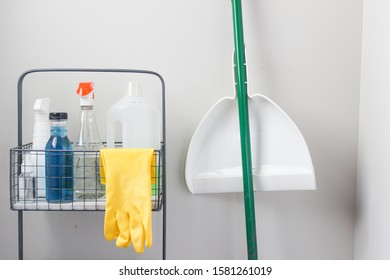 A view of a spring cleaning cart. The cart has cleaning sprays, blue dish detergent and gloves hanging. Beside the cart is a white dustpan on a green broom handle
