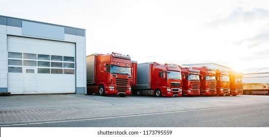 View of squadron group of new red cargo trucks parked in a row near warehouse building in bright sunset light