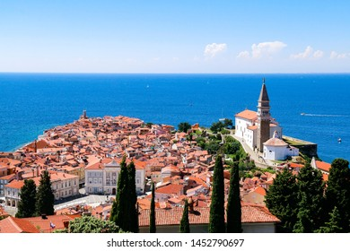 View of St George's Church and the red tiled rooftops of the old town of Piran in Slovenia, with the Adriatic Sea in the background