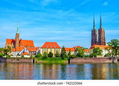View of St. John Cathedral towers and Church of Holy Cross and St. Bartholomew on Tumski Island. Cityscape of  Wroclaw, Poland, Odra River, blue sky.