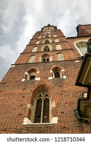 Up view at the façade of St. Mary's gothic church in the Main Market Square of the historic Old Town in Krakow against a cloudy sky.
