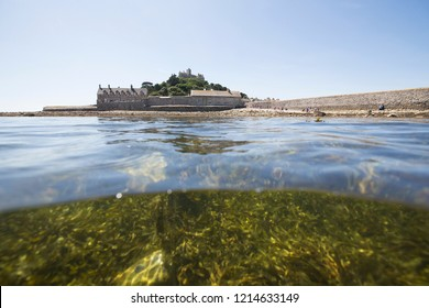 View of St Michael's's Mount, partially from underwater on a summer's day. Part of the view shows seaweed at low tide.
