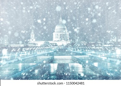 View of St. Paul Cathedral and Millennium Bridge in London by night with snow