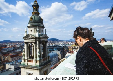 View of St. Stephen's Basilica, a Roman Catholic basilica in Budapest, Hungary, summer sunny day with a female european tourist