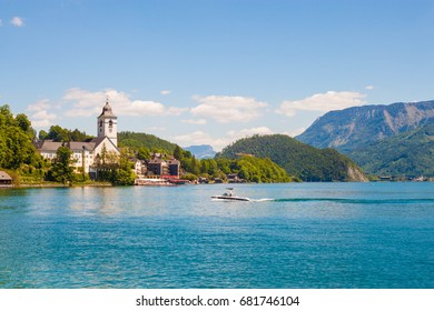 View of St. Wolfgang chapel and the village of St. Wolfgang at Wolfgangsee lake, Austria. Beautiful view of popular touristic austrian town in Salzburg Land.