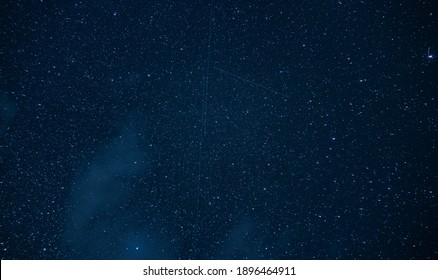 View of a starry night in the middle of the Vladeasa mountains in Romania. The stars, satellites and comets are present to give us the best spectacle with a bluish sky in the background.