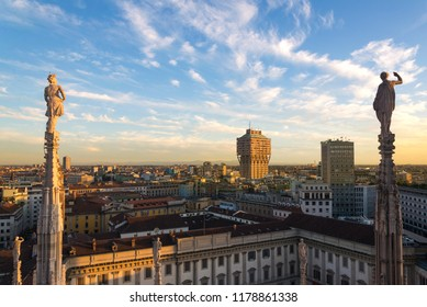 View of statues on the spires and top view cityscape of Milan city from terrace at the rooftop of Duomo di Milano, catholic church, in Milan, Italy with twilight and cloudy sky background.