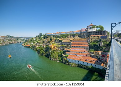 View of steep bank of Douro River in Porto, Portugal, with old wineries on slope and historic buildings of Serra do Pilar Monastery on hilltop.
