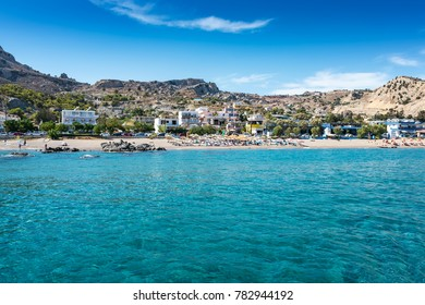 View of Stegna beach with sunshades and sunbeds, boats in background (RHODES, GREECE)
