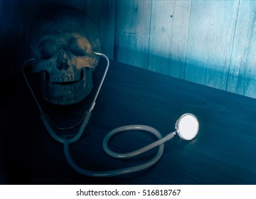 View of stethoscope and skull on wood background. Dark blue tone.