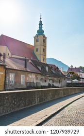 View of a stone street, church and old buildings with dilapidated facades in the old town of Samobor near Zagreb in Croatia on a sunny day, on a sunny day in autumn with natural lens flare.