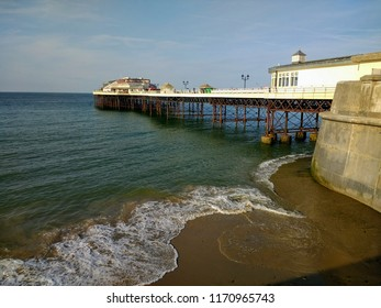 View from the stone wall promenade of the shore in Cromer Norfolk East Anglia across the sandy beach and calm sea waters along the old vintage wooden pier out towards the ocean on holiday in summer