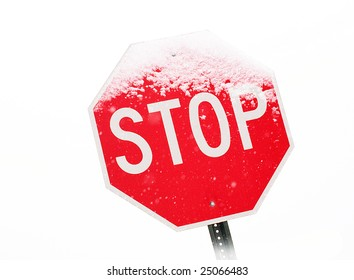 View of stop sign partially covered in snow during a snowstorm.