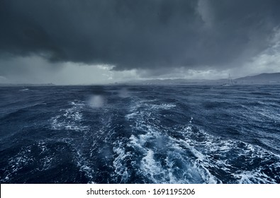 The view of the stormy sea and mountains from the sailboat, Path from foam after the boat, splashes from under the boat, rainy weather, dramatic sky