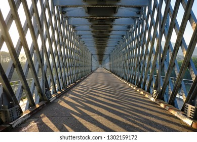View straight down the bridge that connects Tui (Spain) and Valenca (Portugal).  Metal frame, with light and shadows coming through. Geometric square shape to infinity. Built in 1879.