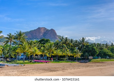 A view of The Strand Townsville, Queensland, Australia. A tropical beach and palm trees in the foreground and rocky hill in the distance.