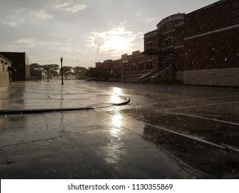 View from a street corner during a Summer rainstorm. Sunbeams breaking through the grey clouds. Rain falling from the sky. Buildings & trees silhouetted against the sky. Reflection on the wet pavement