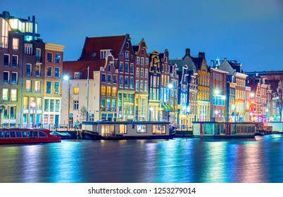 View of streets and canals in the city center at night in AMSTERDAM, NETHERLANDS.