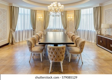 View of stylish and light dining room with big windows and crystal chandelier in center of ceiling. Modern interior of big room with wooden table in center and armchairs around.