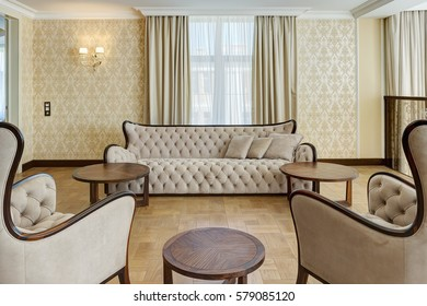 View of stylish and light living room with big windows in beige and brown colors. Classic interior of big room with beige sofa, two armchairs and rounded wooden table.