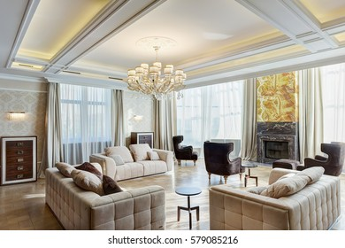 View of stylish and light living room with fireplace, big windows and crystal chandelier in center of ceiling. Modern interior of big room with three beige sofas and armchairs around the fireplace.