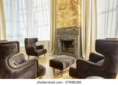 View of stylish living room with fireplace and armchairs around. Interior in brown, beige and golden colors with elements of wood and dark granite. Room with big windows.
