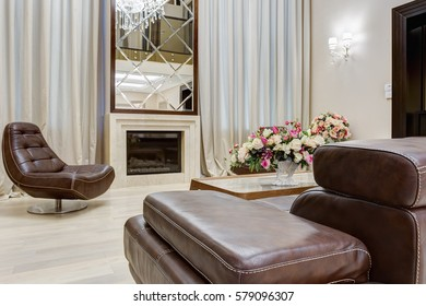 View of stylish living room with fireplace, mirror, leather sofa and armchairs around. Interior in brown, beige and golden. Room with big windows, and flower on table.