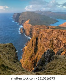 View of the Suduroy coastline and dramatic cliffs just before sunset in the Faroe Islands.