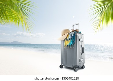 view of  suitcase with hat, pareo and sunglasses on sunny tropic beach